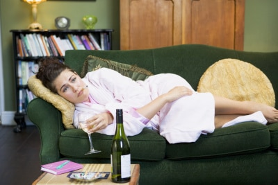 upset woman lying on the couch with a glass of wine