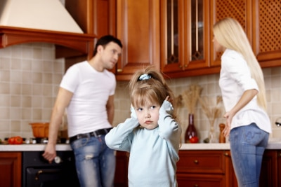 young couple fighting in front of their kid