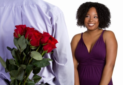 man bringing red roses and courting a black beautiful woman