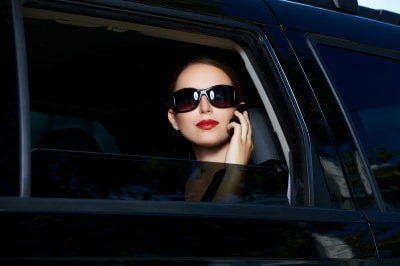 a smart, strong, successful woman on a black car