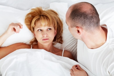 a couple on white bed staring at each other