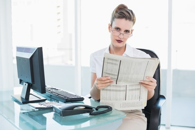 Serious businesswoman wearing glasses holding a newspaper in bright office