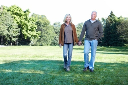 happy matured couple holding hands while walking at the park