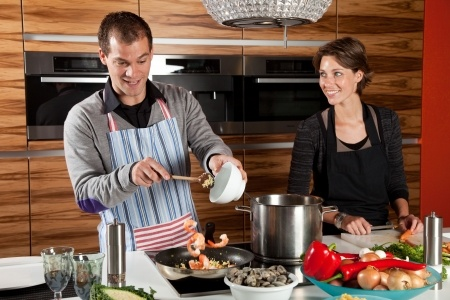 husband and wife cooking together in the kitchen