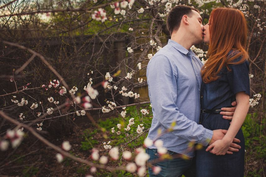 young sweet couple kissing in the garden