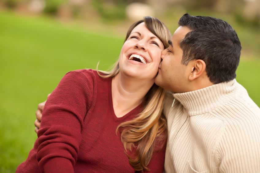a very happy woman kissed by his husband at the park