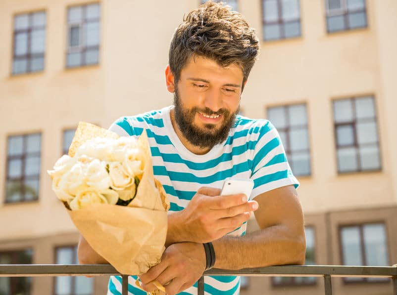 bearded guy holding flowers while texting and hoping to get ex back