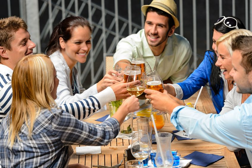 young people celebrating outside and drinking wine
