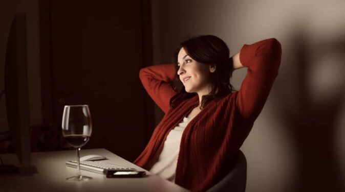 attractive beautiful woman wearing red sweaters sitting and drinking wine while dating online