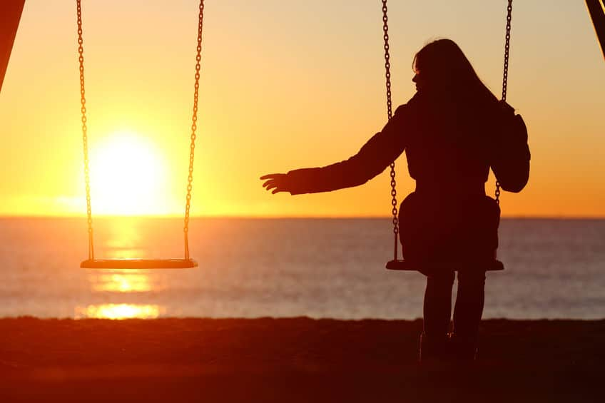 silhouette of woman alone at beach under a beautiful sunset