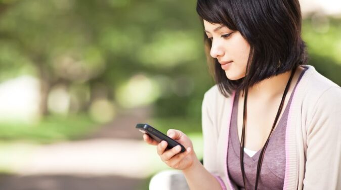 short haired woman using mobile phone at the park