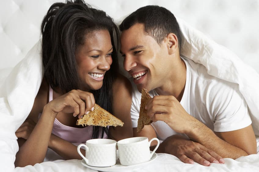 couple eating breakfast together on bed