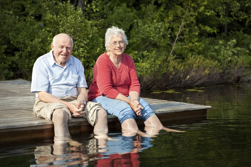 old couple sitting and having a great time in the lake