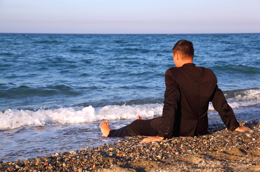 lonely man sitting at the beach