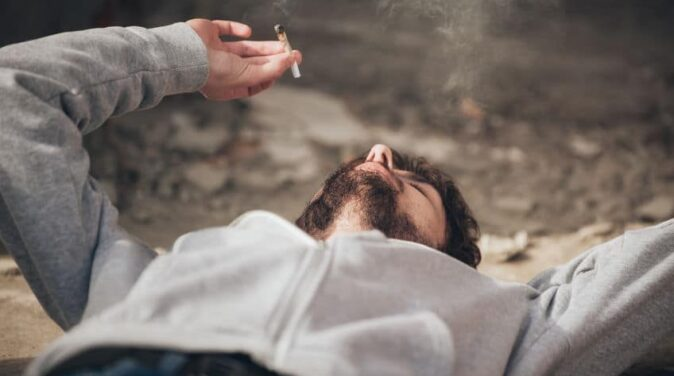 guy lying on the floor while smoking