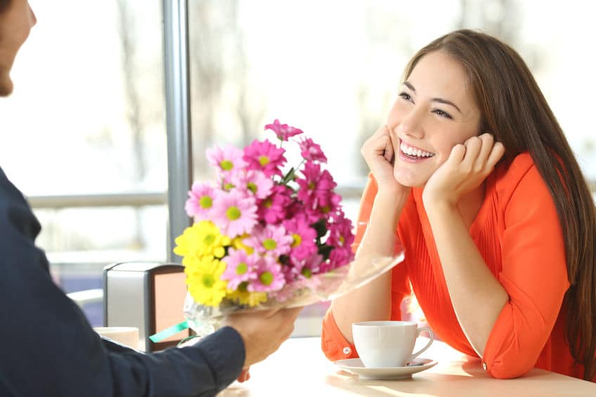 guy giving flowers to a pretty smiling girl