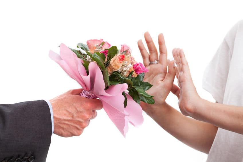 woman rejecting flowers from a guy