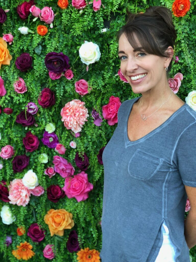 lovely woman taking a picture with a beautiful background with lots of flowers