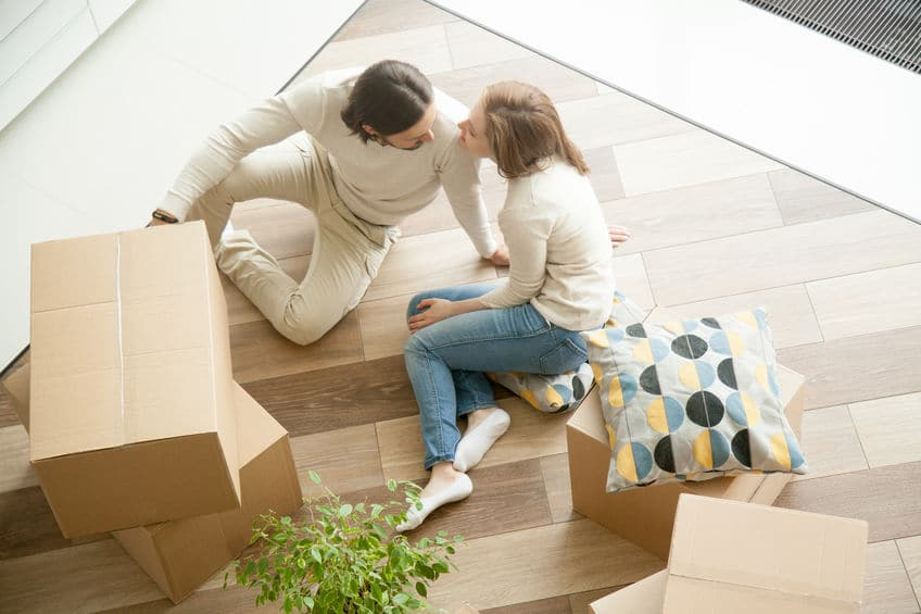 Couple sitting on floor with boxes, moving day, top view