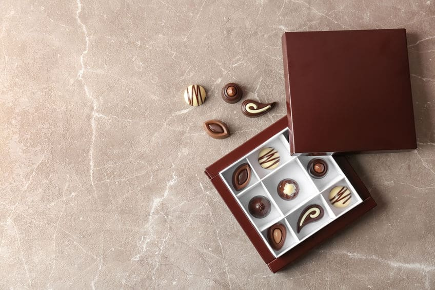 Box with different tasty chocolate candies on table, top view
