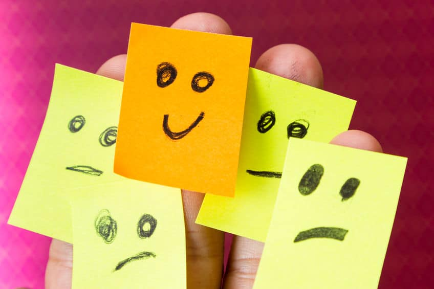 concept for optimism with paper faces on multiple fingers one with a happy good attitude