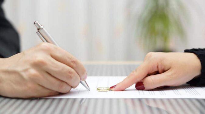 husband signing divorce agreement and woman push away weeding ring