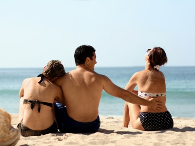 man in between two woman, one holding close to his arms