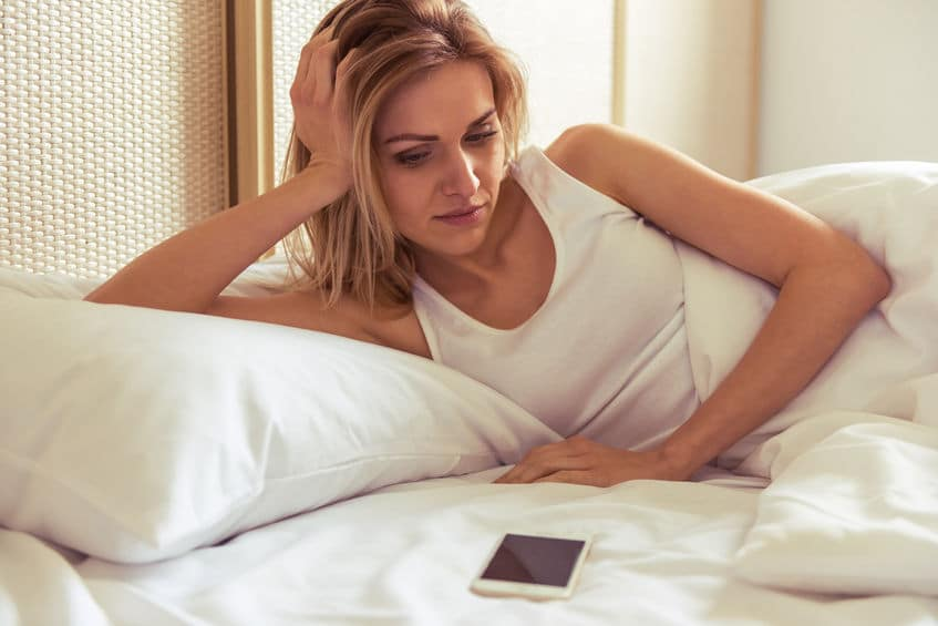 woman lying on bed waiting for a text