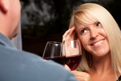 blonde woman holding wine glass, smiling towards the man
