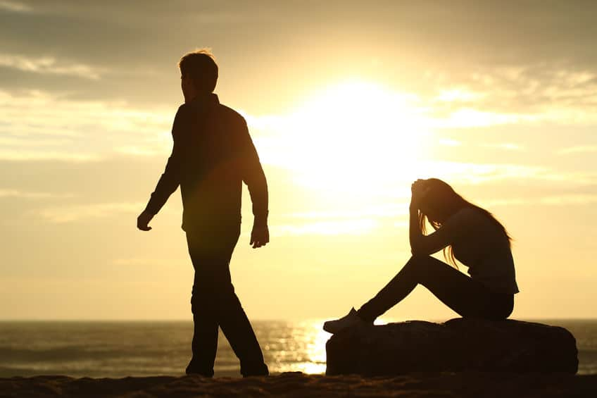 Couple silhouette breaking up a relation on the beach at sunset
