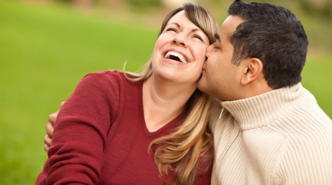 happy woman wearing red sleeve kissed by her husband