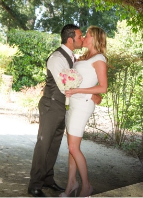 newly-wed couple kissing under the shade of a tree