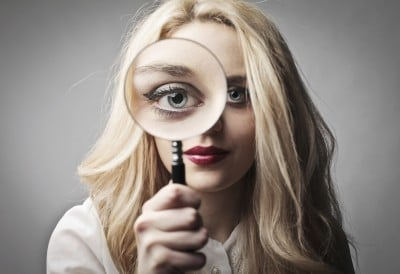 Young woman holding a magnifying glass