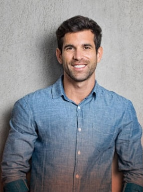 attractive man smiling wearing a blue long sleeve