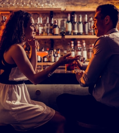 man and woman chatting while drinking at a bar