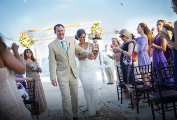 Love U love story of happy couple walking down the aisle with wedding guests applauding