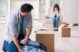 man packing his things while his wife cries on the couch