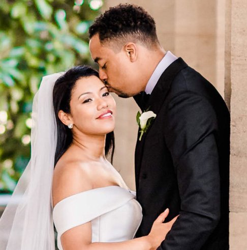 tall and handsome groom kissing his smiling bride wearing a white bridal gown on the forehead