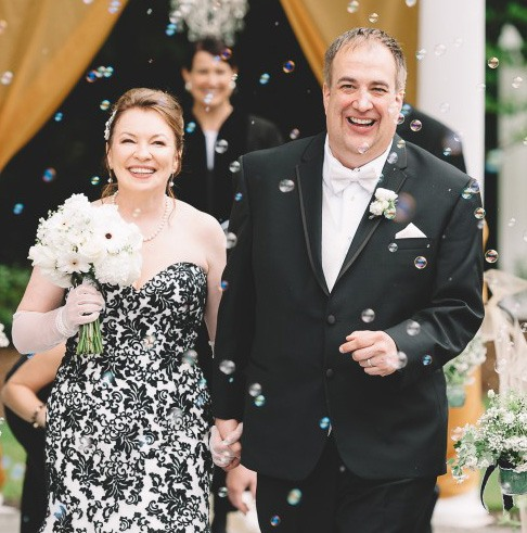 Love U success story of bride wearing a black lace dress holding white flowers with her groom