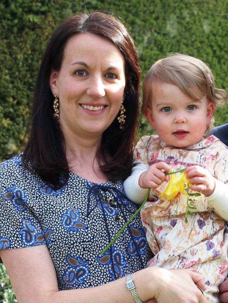 strong smart woman smiling with her adorable baby holding a yellow flower