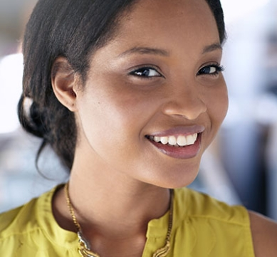 young, woman of color wearing a yellow sleeveless top