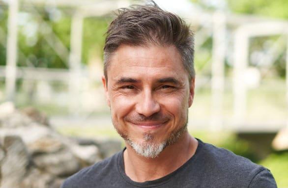 a bearded man wearing a dark grey shirt, smiling