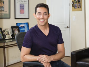 smiling Evan Marc Katz dating coach wearing a purple T-shirt