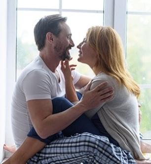 sweet couple sitting next to a window, cuddling