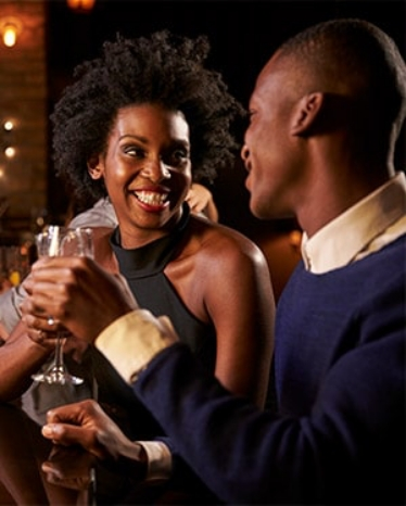 man and woman flirting on a bar while having drinks