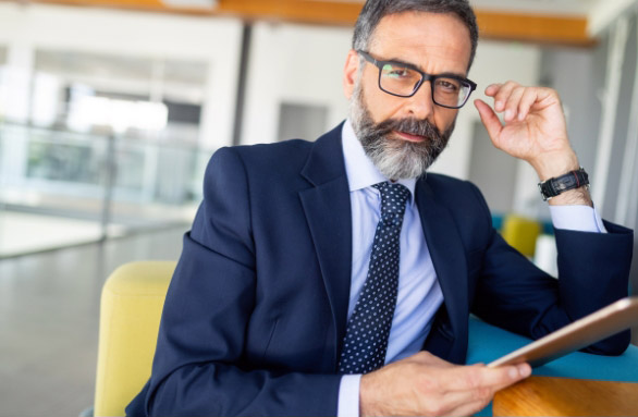 bearded businessman wearing eyeglasses while holding a file