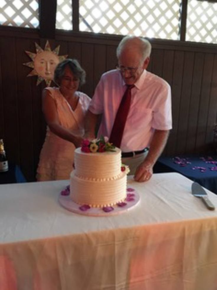 Love U success story of a happy couple smiling while slicing a cake.