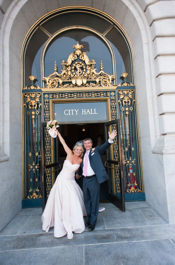 happily married couple at the entrance of the city hall