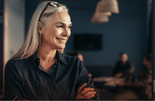 confident smart strong successful woman with long white hair smiling and crossing her arms