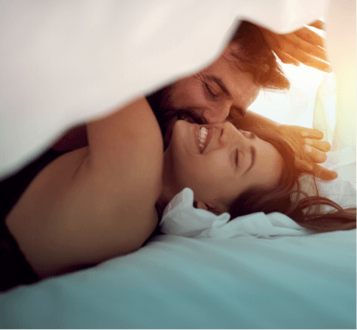 Love U success story couple cuddling and laughing under the bed sheets